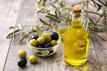 Virgin olive oil in a crystal bottle on wooden background