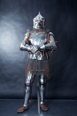 A medieval warrior in a helmet and with a sword. Knight on dark background