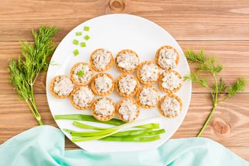 Тарталетки с салатом из сайры и яиц выложены на тарелке в виде рыбы.