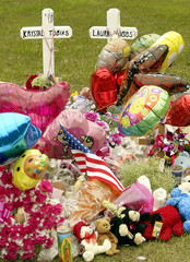A memorial for two slain girls sits in a nature area.