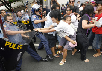 woman activist grab the wooden stick of a riot policeman during a scuffle outside the U.S. embassy in Manila