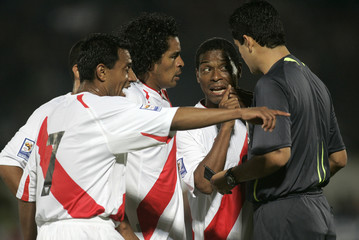 Peru's Solano Acasiete and Jayo talk with referee during their 2010 World Cup qualifying soccer match against Chile in Santiago