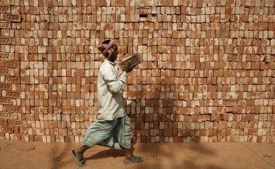 A labourer carries bricks in the northeastern Indian city of Siliguri