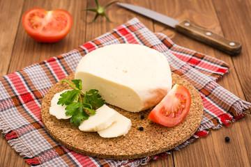 Нарезанный сыр, помидор и листья петрушки на подложке на деревянном столе