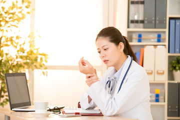 doctor suffering from wrist pain in clinic