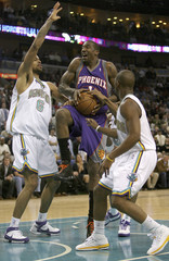 Phoenix Suns Stoudemire goes up for a shot as he is guarded by New Orleans Hornets center Chandler and guard Paul during the first half of their NBA basketball game in New Orleans