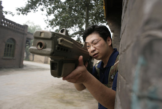 """A customer of Xuelang Outdoor Sports Club uses a laser gun during a """"Counter-Strike"""" game in Beijing"""