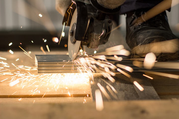 Master sawing metal, sparkles with bright sparks