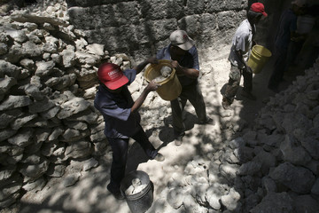 Workers carry limestone at a cement processing factory in Samaria town
