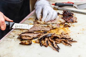 Chef slicing grilled beef steak