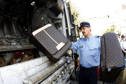 A French customs officer throws counterfeit luxury luggage into a garbage truck for destruction in Cannes
