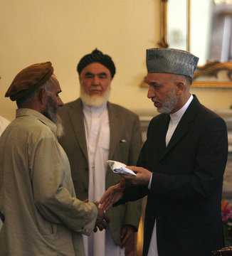 Afghan President Hamid Karzai gives some money to an Afghan man in Kabul