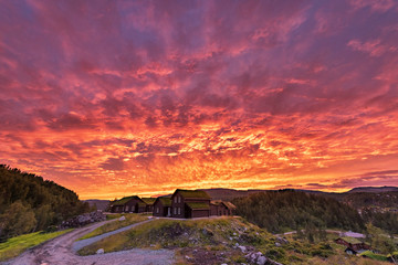 Papiers peints Grenat Burning Sky in Norway. Local Village Architecture and Red Sky.