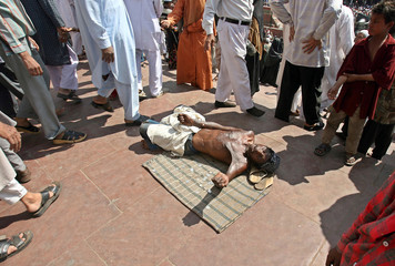 Indian man begs outside Jama Masjid mosque after Friday prayers in old quarters of Delhi
