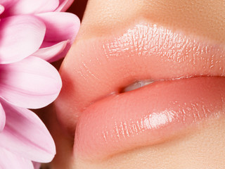 Lips augmentation. Perfect natural lip makeup. Close up macro photo with beautiful female mouth. Plump full lips. Close-up face detail. Perfect clean skin, light fresh lip make-up