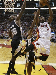 San Antonio Spurs' Francisco Elson defends Miami Heat's Dwyane Wade during their NBA game in Miami