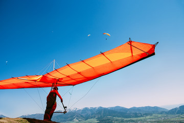 Wall Murals Sky sports Man with hang-glider start to fly on the top of hill
