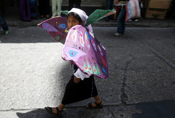 A young girl wears butterfly wings as she marches in an International Women's Day parade in Guatemala City