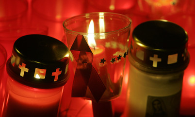 A red ribbon, an anti-Aids symbol, is attached to a candle after a commemoration march by AIDS activists in downtown Berlin