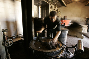 A worker prepares to press olive paste to extract oil at a traditional oil works in the eastern village of Tazmelt