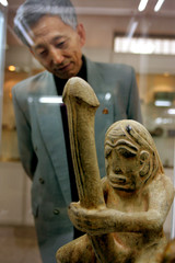 Chinese doctor Ma Xiao-nian looks at statue in Beijing institute.