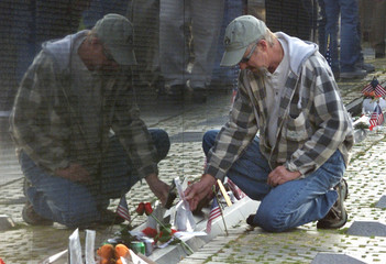 A MAN LEAVES MEMORBILIA ON THE GROUND AT THE VIETNAM VETERANS MEMORIALWALL IN WASHINGTON.