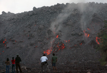 Villagers look at molten rocks accumulated at base of Mount Mayon volcano in Legazpi city, south of Manila