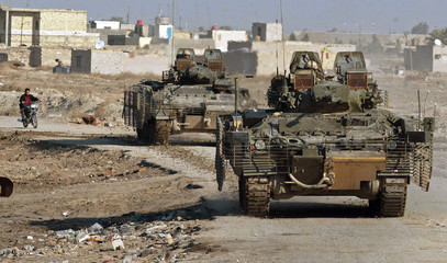 British armoured vehicles approach scene of roadside bomb attack in southern Iraq city of Basra