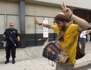 PROTESTER PASSES OFFICER WITH RIOT GEAR IN MIAMI.