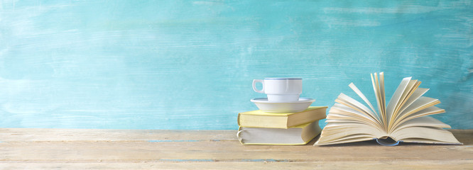 opened book, cup of coffee on grungy background, panoramic, copy space