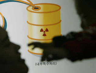 A SOUTH KOREAN WOMAN HUGS HER BABY IN FRONT OF THE SYMBOL OF NUCLEARENERGY AT THE SCIENCE ...