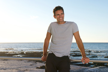 handsome middle age man smiling by sea