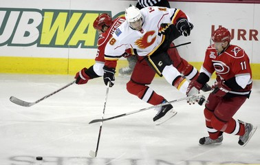 Carolina Hurricanes'  Hedican collides with Calgary Flames' Lombardi as Williams skates past during the third period of their NHL hockey game in Raleigh