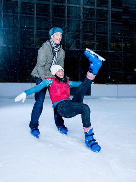 Man supporting woman as she falls while iceskating