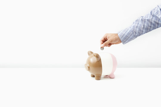 Man putting coin in piggy bank