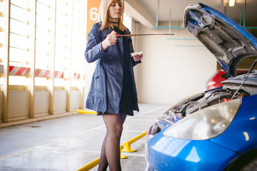 woman near car's hood. young blonde in covered parking of shopping center, stands near car with raised engine compartment hood, checks engine oil level in engine, inspects feeler gauge