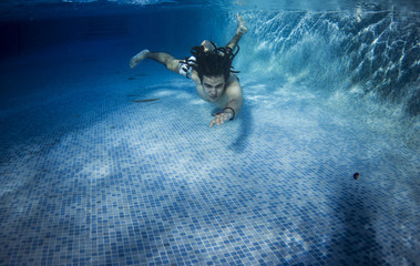 Young man underwater at the pool on a summer day