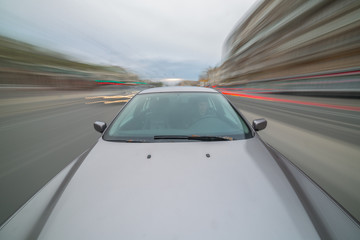 Front view of black car driving on high speed on a city at day time.