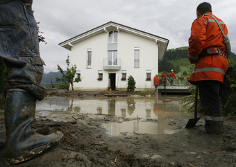 Rescue workers stand in front of a flooded house a violent thunderstorm in Gross