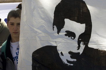 An Israeli youth stands beside a banner depicting Israeli soldier Shalit, during a demonstration outside Israel's PM Olmert's residence in Jerusalem