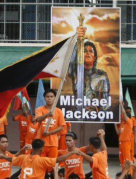 A prison inmate waves a Philippine flag during a tribute to late pop icon Michael Jackson at prison grounds in Cebu