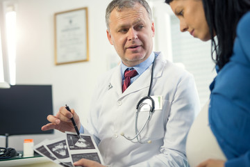 Gynecologist doctor showing ultrasound image to pregnant woman at hospital