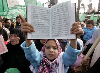 Palestinian girl holds up copy of Koran during Hamas rally against Prophet Mohammad's offensive cartoons in Gaza
