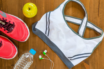 sports bra and sneakers for fitness a top view of the wooden floor