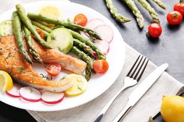 Steak of salmon with asparagus, vegetables, fork and knife
