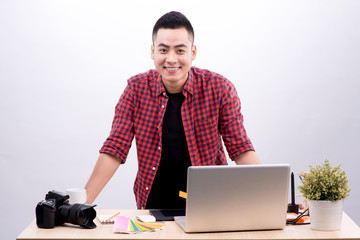 Professional photographer. Portrait of confident young man in shirt holding hand on camera while sitting at his desk.