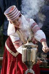 A women dressed in Belarussian national clothes pours water from a samovar to make tea during a harvest festival in Bobruisk