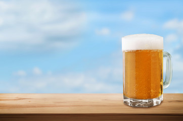 Cold beer on wooden table on sky background