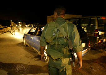 A PALESTINIAN POLICEMAN INSPECTS PALESTINIAN VEHICLE ON A ROAD ADJACENTTO DUGIT JEWISH SETTLEMENT ...