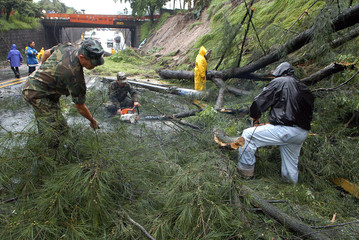 Salvadoran soldiers and public works employees try to clear landslide debris in San Salvador